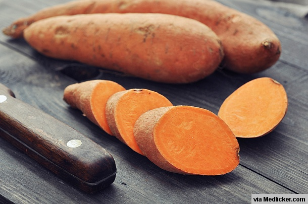 Raw sweet potatoes on wooden board