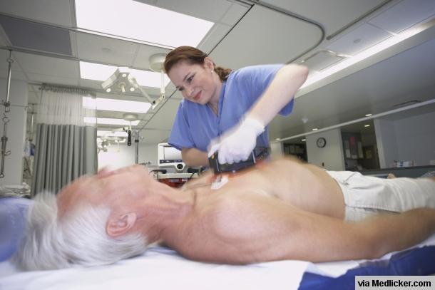 Sestřička defibriluje starého pacienta