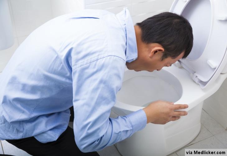 Muž zvrací do záchodové mísy při kocovině