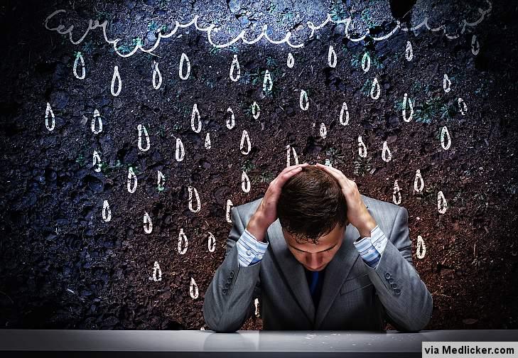 Muž v depresi se drží za hlavu a prší na něj z mraku