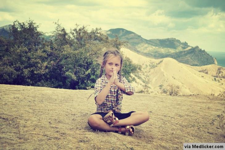 Holčička medituje v přírodě