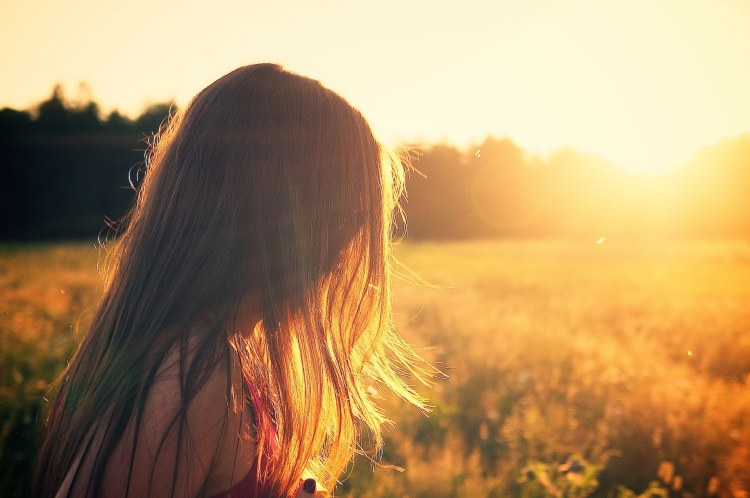 Girl with shiny hair on sunlit summer field