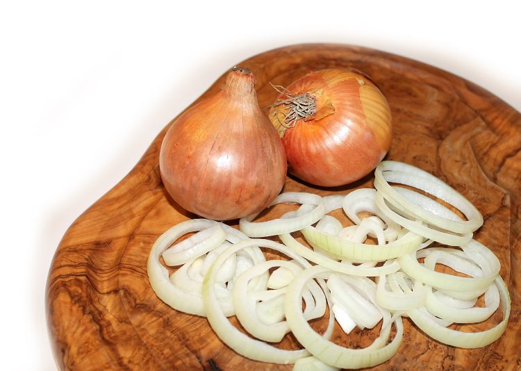 Sliced onions on wooden board