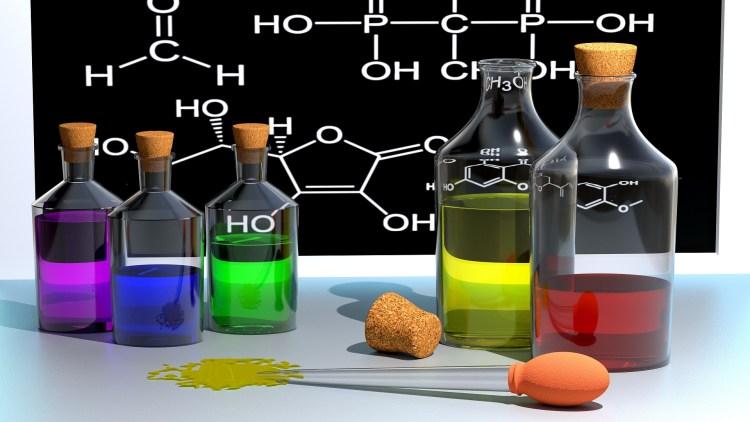 Chemická laboratoř s kádinkami s barevným obsahem
