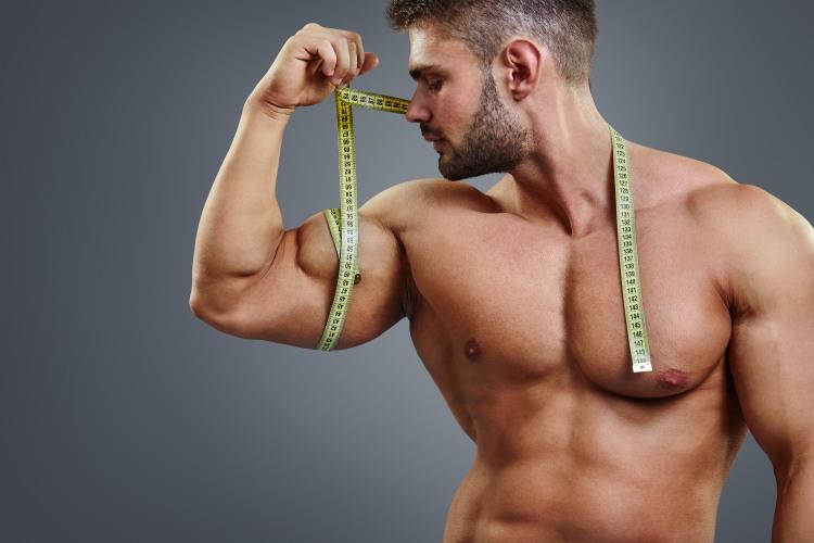 Muž s velkými svaly a metrem