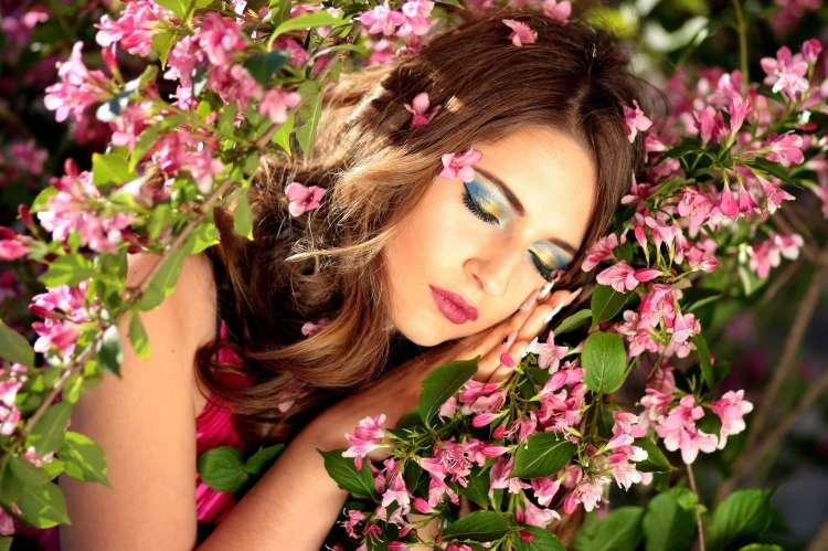 Fille qui dort dans une prairie avec des fleurs roses