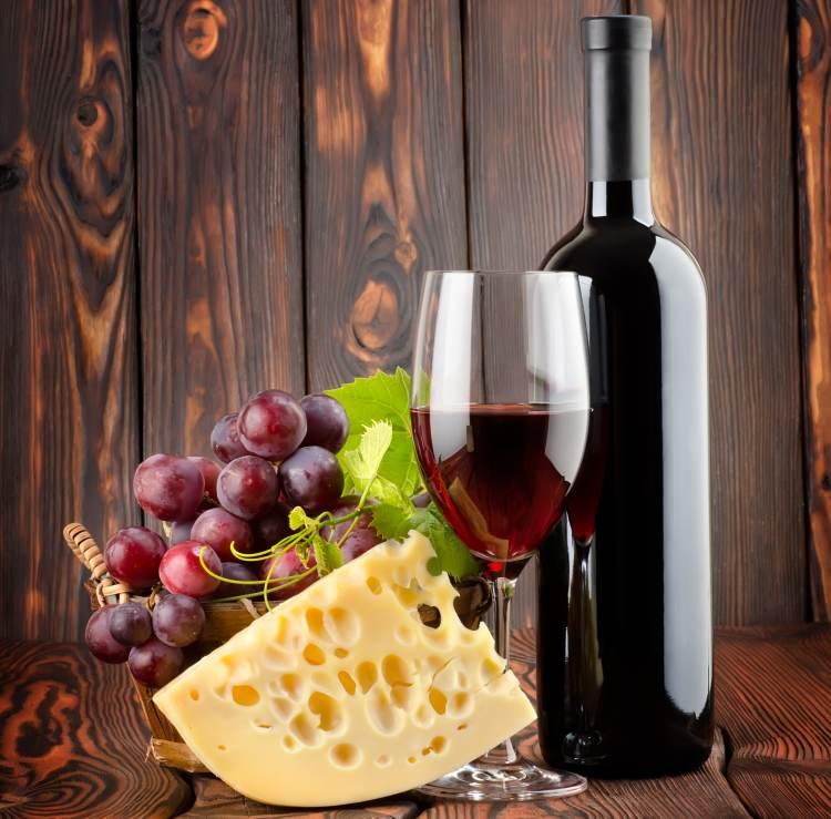 Červené víno, sýr a hrozny na stole