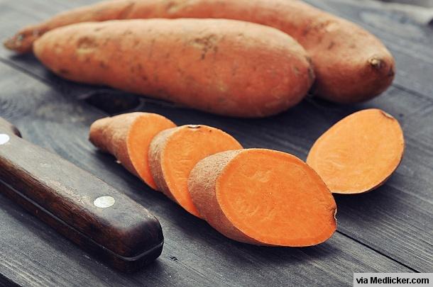 Raw sweet potatoes on wooden board