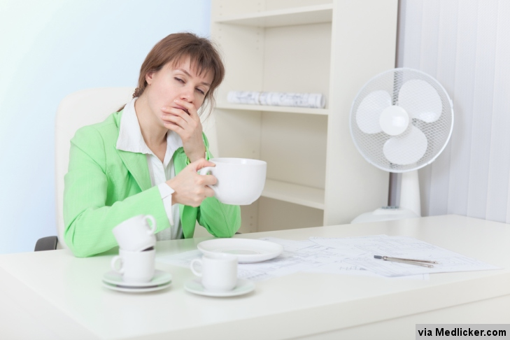 Zívající dívka u stolu s ventilátorem