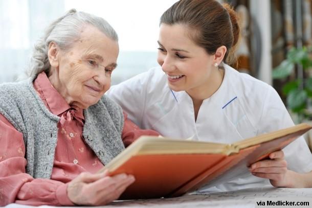 Zdravotná sestra číta knihu starej paní
