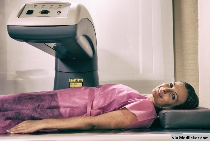 Žena na vyšetření hustoty kostí - kostní denzitometrie