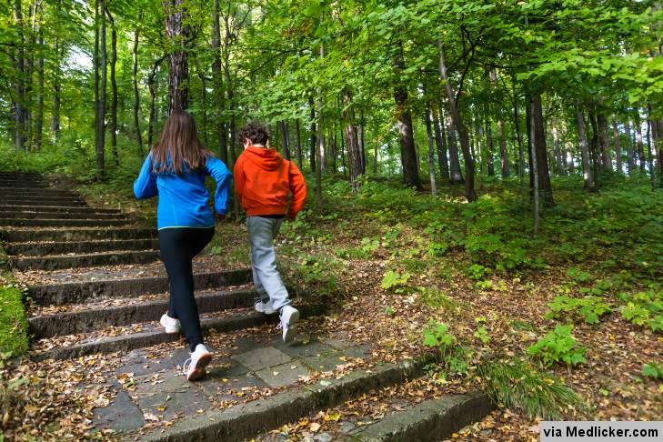 Kluk a holka běží po schodech v lese