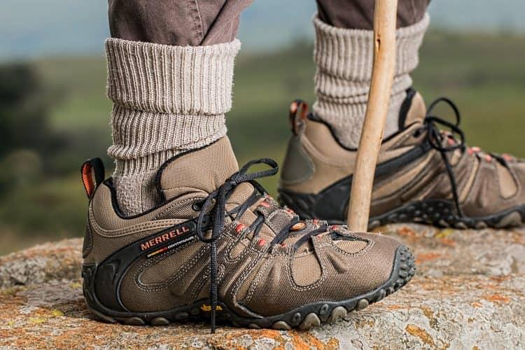 Chůze v horách - nohy s botami a holí