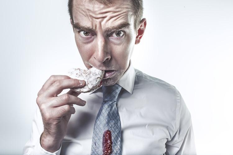 Hladový muž jí a má špinavou kravatu