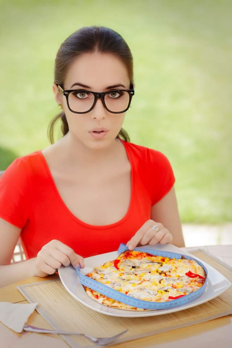 Žena měří pizzu krejčovským metrem